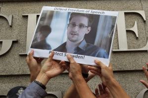 Protesters in support of Edward Snowden, a contractor at the National Security Agency (NSA), hold a photo of him during a demonstration outside the U.S. Consulate in Hong Kong in this June 13, 2013 file photo. Snowden, left Hong Kong on a flight for Moscow on June 23, 2013 and his final destination may be Ecuador or Iceland, the South China Morning Post said. REUTERS/Bobby Yip/Files (CHINA - Tags: POLITICS CIVIL UNREST)